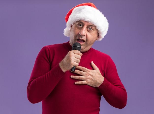 Glücklicher mann mittleren alters mit weihnachtsmütze mit mikrofon, der über lila wand singt