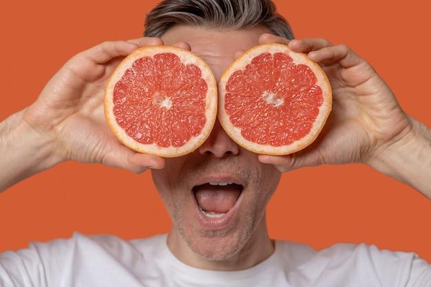 Glücklicher mann. nahaufnahme eines erwachsenen mannes mit offenem mund, der hälften appetitlicher graperut auf augenhöhe hält