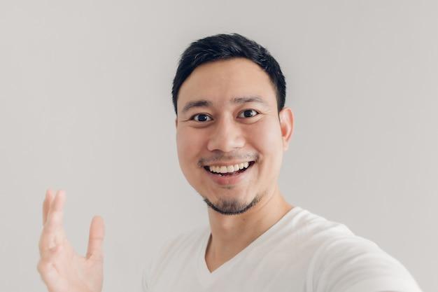 Glücklicher mann nimmt selfie von sich und stellt den leeren kopienraumhintergrund dar.