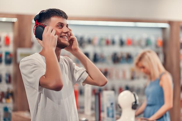 Glücklicher mann posiert mit kopfhörern im tech store. technologie-shopping-konzept.