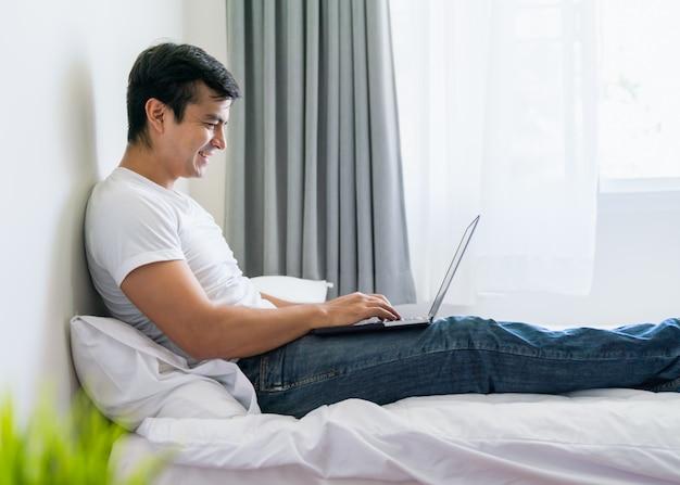 Glücklicher mann relex unter verwendung des laptops auf bett im schlafzimmer