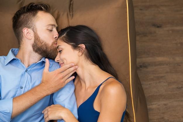 Glücklicher mann seine frau zu küssen, wenn sie auf sofa liegend