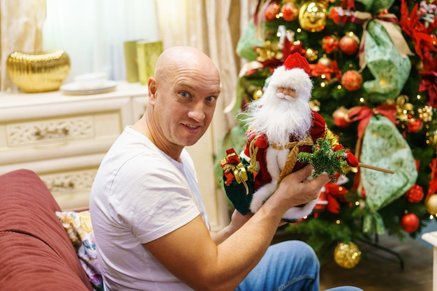 Glücklicher mann sitzt auf dem sofa und hält ein weihnachtsmann-spielzeug auf dem hintergrund eines geschmückten weihnachtsbaums im zimmer ...