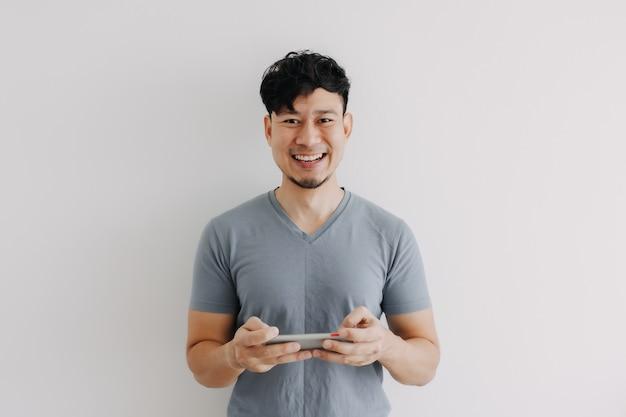 Glücklicher mann spielt online-handyspiel isoliert auf weißem hintergrund