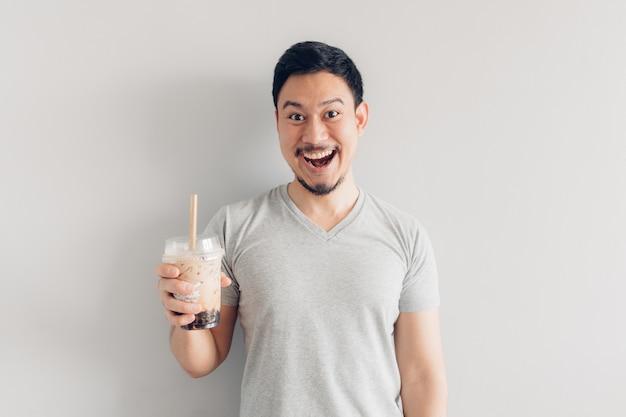 Glücklicher mann trinkt blase milch-tee oder perle milch tee. populärer milchtee in asien und taiwan.