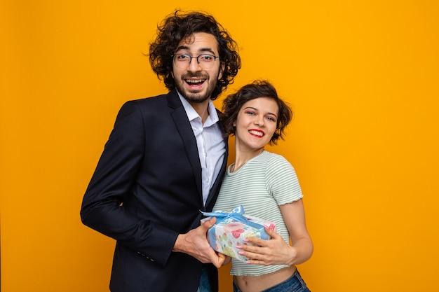 Glücklicher mann und die frau des jungen schönen paares mit dem geschenk, das die kamera lächelt, die fröhlich feiert, den internationalen frauentag 8. märz, der über orange hintergrund steht