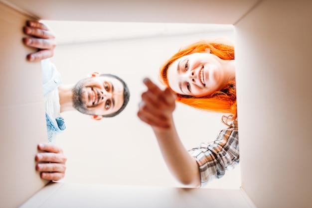 Glücklicher mann und frau, blick aus dem karton, umzug in neues haus. junges paar, einweihungsparty