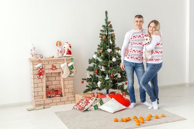 Glücklicher mann und frau des feiertagskonzepts am weihnachtsbaum zu hause