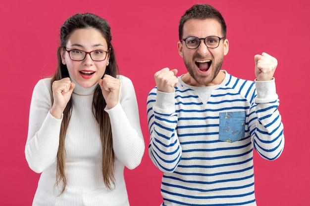 Glücklicher mann und frau des jungen schönen paares in der freizeitkleidung, die die glücklichen und aufgeregten geballten fäuste der brille trägt, die das valentinstagkonzept feiern, das über rosa wand steht