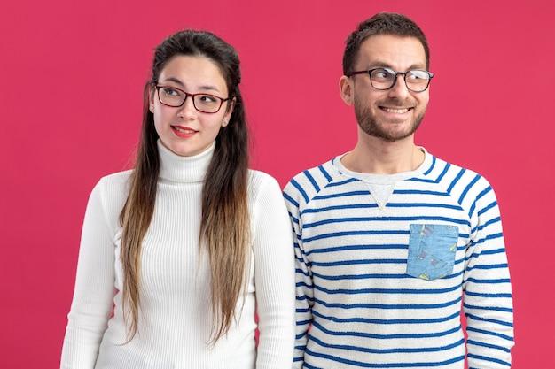 Glücklicher mann und frau des jungen schönen paares in der freizeitkleidung, die mit lächeln auf glücklichen gesichtern beiseite schaut, die valentinstagkonzept feiern, das über rosa wand steht