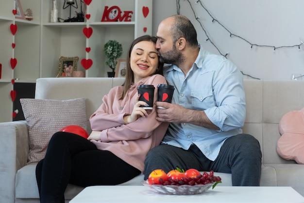 Glücklicher mann und frau des jungen schönen paares mit kaffeetassen, die in der liebe glücklich sind