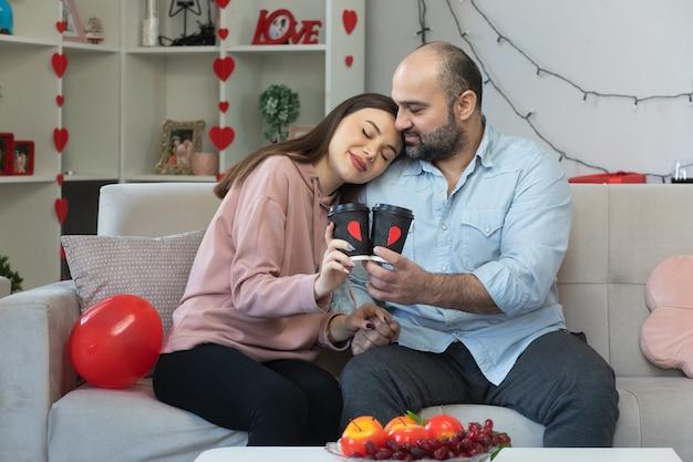 Glücklicher mann und frau des jungen schönen paares mit kaffeetassen, die in der liebe glücklich zusammen umarmen, den internationalen frauentag zu feiern, der auf einer couch im hellen wohnzimmer sitzt