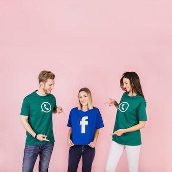 Glücklicher mann und frau, die auf ihren freund verwendet facebook-t-shirt zeigt