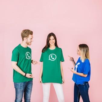 Glücklicher mann und frau, die auf ihren freund verwendet whatsapp t-shirt zeigt