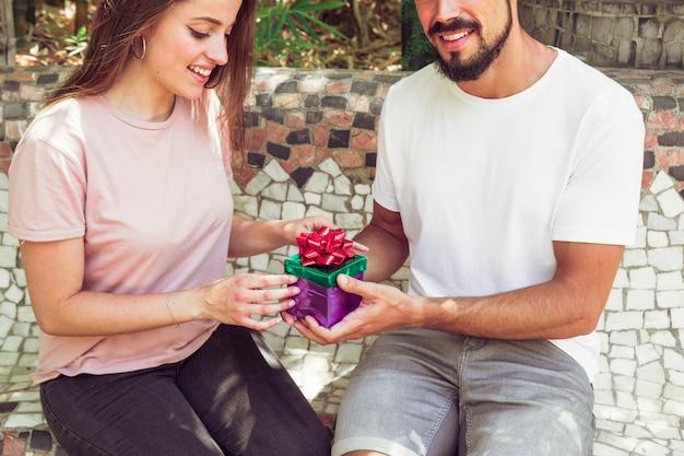 Glücklicher mann und frau, die geschenkbox hält