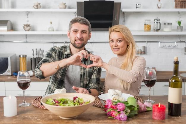Glücklicher mann und frau, die herz durch hände zeigt und bei tisch in der küche sitzt