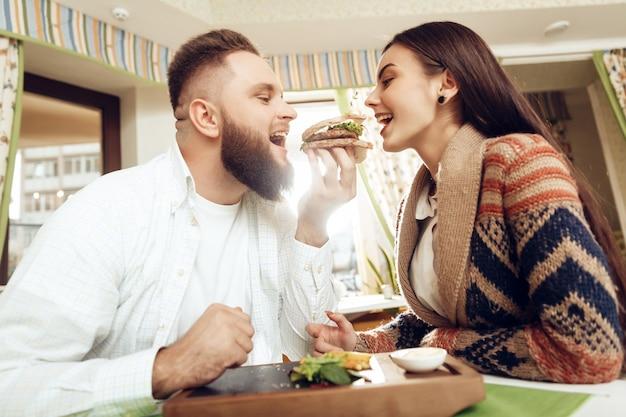 Glücklicher mann und frau, die in einem restaurant zu mittag isst