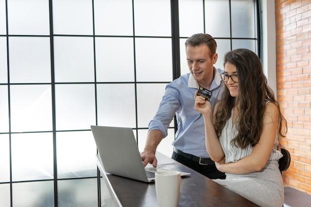 Glücklicher mann und frau, die kreditkarte unter verwendung des laptopeinkaufs online im kaffeehauscafé halten