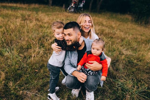 Glücklicher mann und frau, die mit kindern draußen spielen