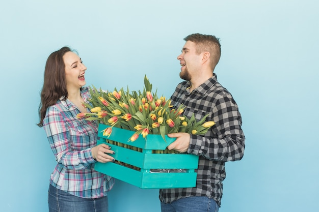 Glücklicher mann und frau floristen halten box mit tulpen und lachen auf blauem hintergrund
