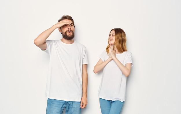 Glücklicher mann und frau in den jeans und in den t-shirts auf einer hellen beschnittenen ansicht.