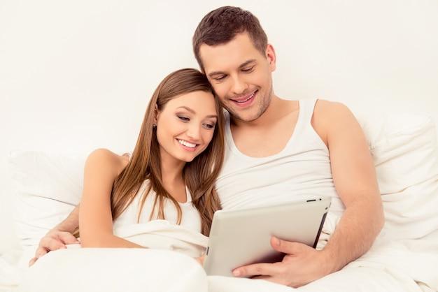 Glücklicher mann und frau in der liebe, die nachrichten auf tablette liest