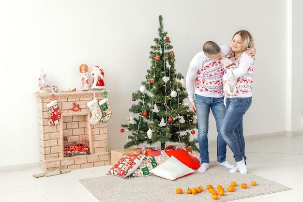 Glücklicher mann und frau nahe weihnachtsbaum zu hause