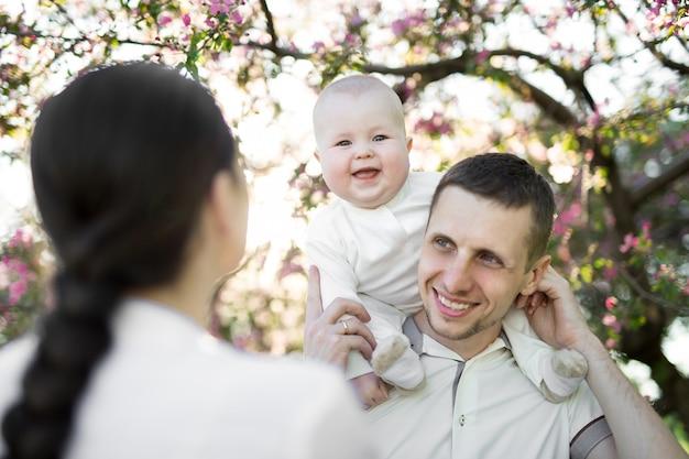 Glücklicher mann und frau spielen mit baby im freien