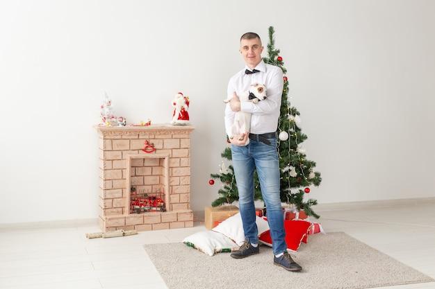 Glücklicher mann und hund zu hause mit weihnachtsbaum