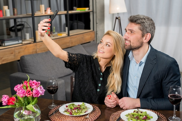 Glücklicher mann und nette frau, die bei tisch selfie auf smartphone nimmt