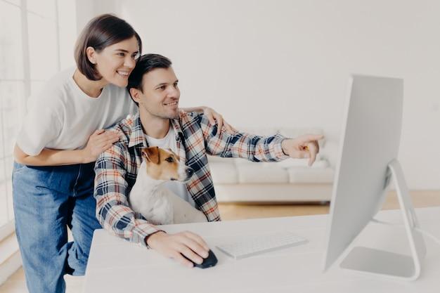 Glücklicher mann und seine freundin beraten sich über zukünftiges projekt, zeigen in monitor, werfen am arbeitsplatz zusammen mit hund im hauptinnenraum auf