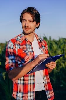 Glücklicher mannlandwirt, der auf einem maisgebiet die kontrolle über den ertrag übernimmt - inage steht