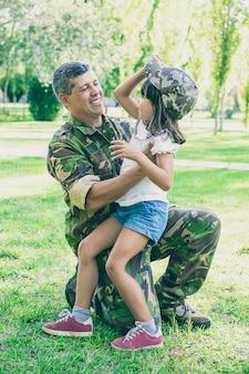 Glücklicher militärischer vater, der tochter nach rückkehr von der missionsreise umarmt