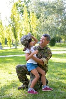 Glücklicher militärischer vater, der tochter umarmt, nachdem er von der missionsreise zurückkehrt. mädchen, das die tarnkappe des vaters anprobiert. familientreffen oder rückkehr nach hause konzept