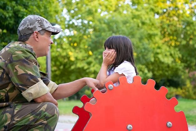 Glücklicher militärischer vater, der zeit mit kleiner tochter im spielplatz genießt, mit mädchen spricht und spielt, während sie mädchen, das schaukeligel reitet. elternschafts- oder kindheitskonzept