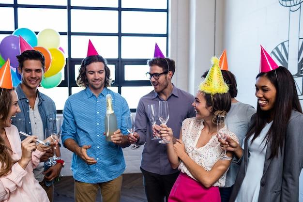 Glücklicher mitarbeiter, der eine flasche champagner für geburtstag öffnet