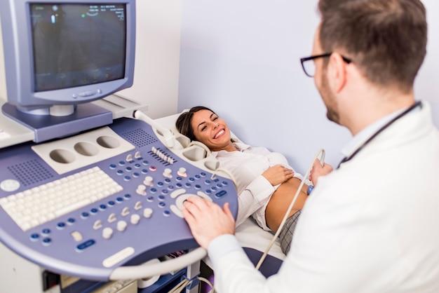 Glücklicher mittlerer patient der erwachsenen frau, der abdomenultraschall an der klinik durchläuft