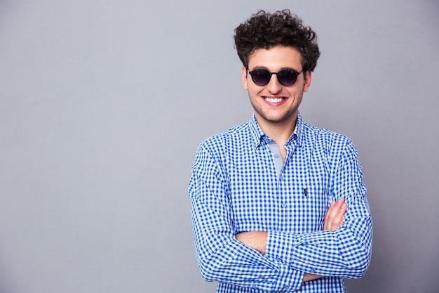Glücklicher mode-mann, der in der sonnenbrille steht, die mit den armen über grauem hintergrund steht
