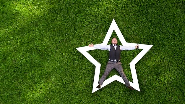 Glücklicher moderator mit einem mikrofon auf dem grünen rasenansicht von oben luftaufnahme mit drohne