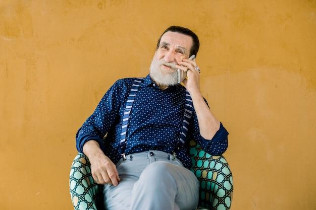 Glücklicher moderner trendiger grauer bärtiger mann im stilvollen dunkelblauen hemd, in den hosenträgern und in der grauen hose, die auf dem stuhl auf gelbem hintergrund sitzen und telefon sprechen