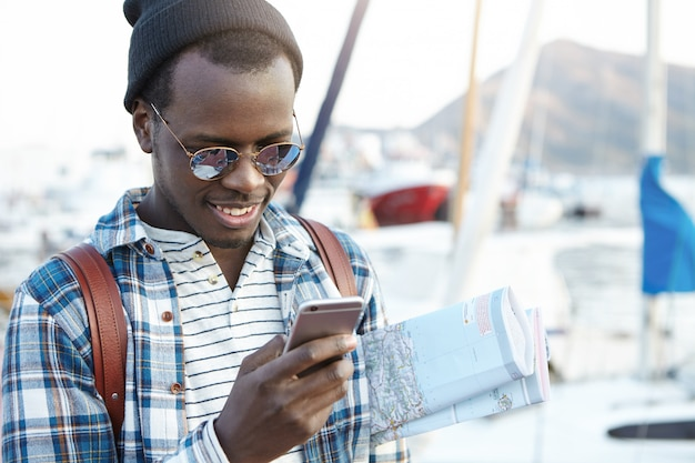 Glücklicher modischer dunkelhäutiger mann, der allein im europäischen ferienort mit papierkarte unter seinem arm reist und nach café und herbergen in der nähe mit 3g oder 4g internetverbindung auf seinem handy sucht