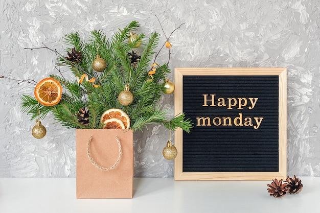 Glücklicher montag-text auf tafel und festlichem blumenstrauß von tannenzweigen mit weihnachtsdekor im handwerkspaket auf tabelle