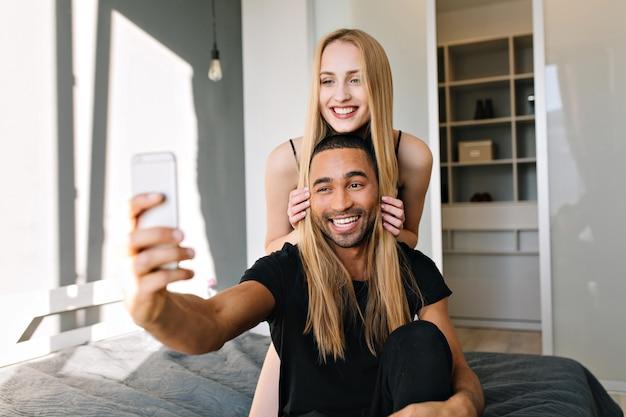 Glücklicher morgen in der modernen wohnung des freudigen paares, das spaß zusammen hat. selfie machen, wahre positive emotionen, liebe, freizeit, fröhliche stimmung, lächeln, freude, zusammengehörigkeit ausdrücken