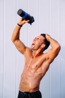 Glücklicher muskulöser kerl, der wasser von der flasche auf seinem körper ausläuft, schwitzend nach training