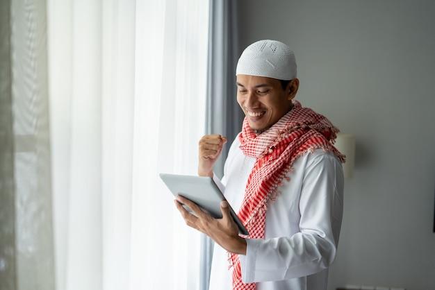 Glücklicher muslimischer geschäftsmann, der lächelt, während tablet-pc nahe fenster verwendet