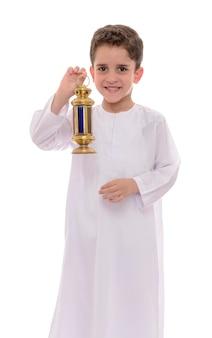 Glücklicher muslimischer junge, der weißen djellaba trägt, der ramadan feiert