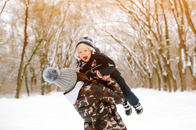 Glücklicher mutter- und schätzchensohn, der spaß zusammen am winterpark hat