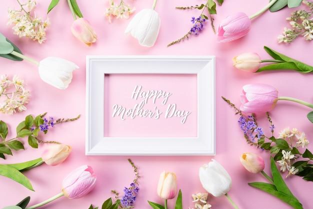 Glücklicher muttertag mit draufsicht von rosa tulpenblumen und von weißem bilderrahmen
