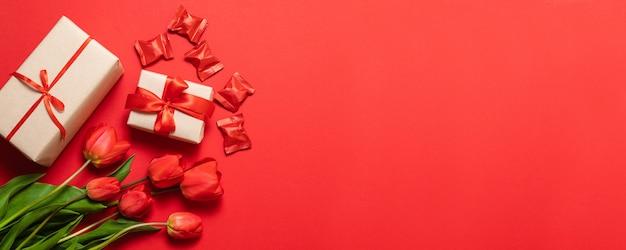 Glücklicher muttertagestext und schöne rote tulpen mit geschenkbox auf rotem hintergrund. glückliche muttertagesgrußkarte mit frühlingsblumen.