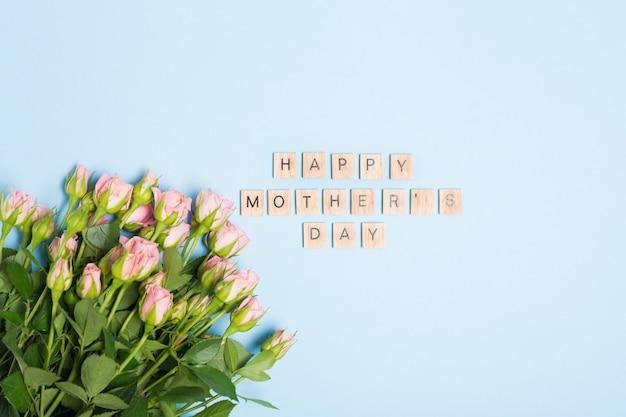 Glücklicher muttertagstext und rosa rosen auf blauem hintergrund. freiraum. flach liegen. draufsicht.